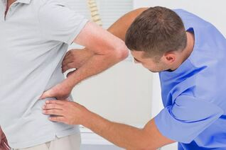 Patient with low back pain on diagnostic examination by a doctor